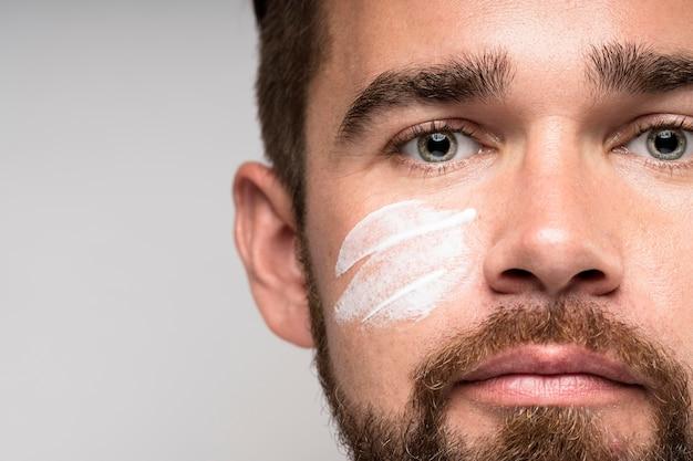 Retrato de homem bonito usando creme facial com espaço de cópia