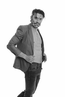 Retrato de homem bonito usando máscara para se proteger da infecção covid-19, filmado em preto e branco