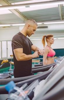 Retrato de homem bonito, verificando a frequência cardíaca no relógio durante um treinamento duro em esteira no centro de fitness. conceito de esporte e tecnologia.