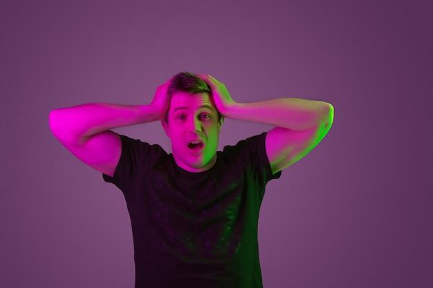 Retrato de homem branco isolado em estúdio roxo em luz de néon