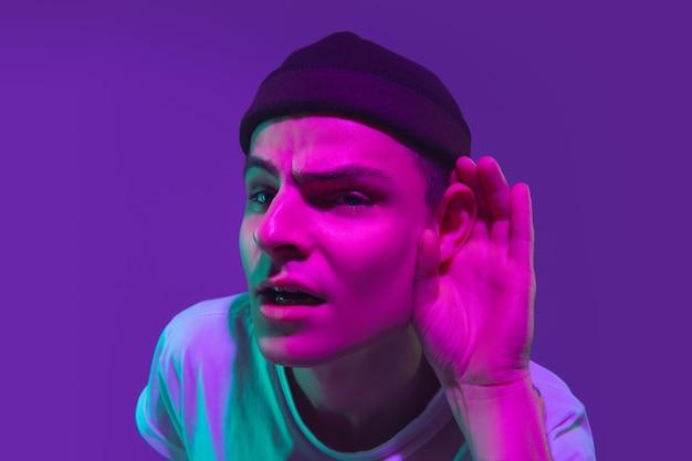 Retrato de homem branco isolado no fundo roxo do estúdio em luz de néon