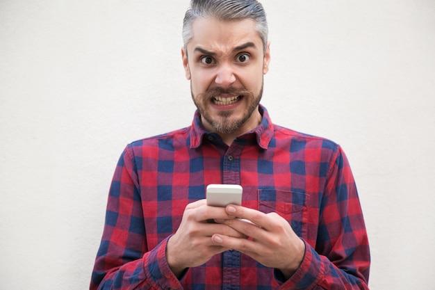 Retrato de homem bravo, usando telefone celular