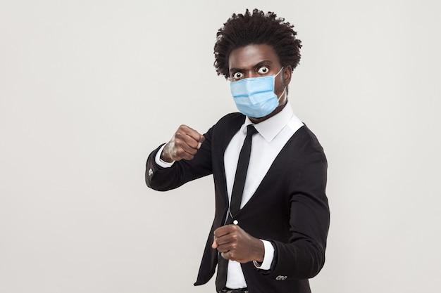 Retrato de homem bravo, vestindo um terno preto com máscara médica cirúrgica em pé com punhos de boxe e pronto para atacar ou defesa. estúdio interno tiro isolado em fundo cinza.