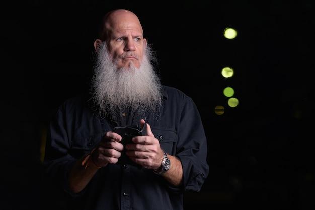 Retrato de homem calvo bonito maduro com barba grisalha ao ar livre à noite