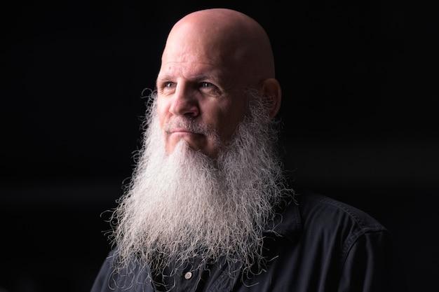Retrato de homem calvo bonito maduro com barba grisalha pensando ao ar livre à noite
