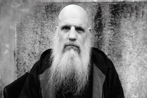 Retrato de homem calvo maduro com longa barba grisalha contra parede de concreto grunge ao ar livre em preto e branco