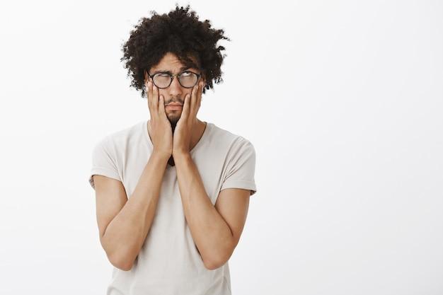 Retrato de homem cansado e irritado de óculos, revirando os olhos e com a palma da mão incomodada