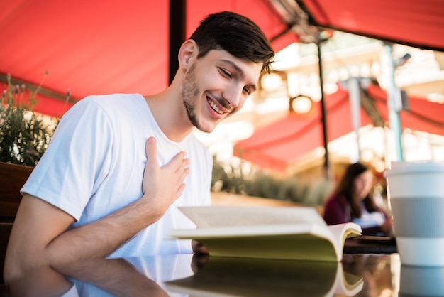 Retrato de homem caucasiano, aproveitando o tempo livre e lendo um livro enquanto está sentado ao ar livre na cafeteria. conceito de estilo de vida.