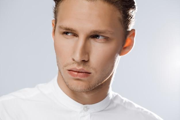 Retrato de homem caucasiano atraente sobre parede branca.