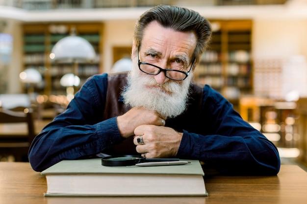 Retrato de homem caucasiano barbudo sênior de óculos a sorrir, sentado à mesa com livro, lupa e caneta, sobre fundo interior de biblioteca antiga vintage