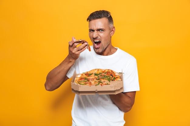 Retrato de homem caucasiano de 30 anos em uma camiseta branca segurando e comendo pizza em pé isolado em amarelo