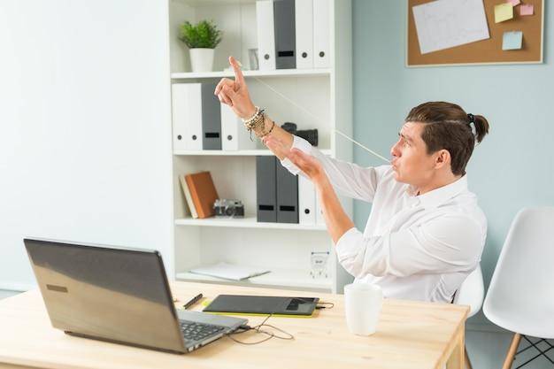 Retrato de homem caucasiano esticando chiclete da boca no escritório