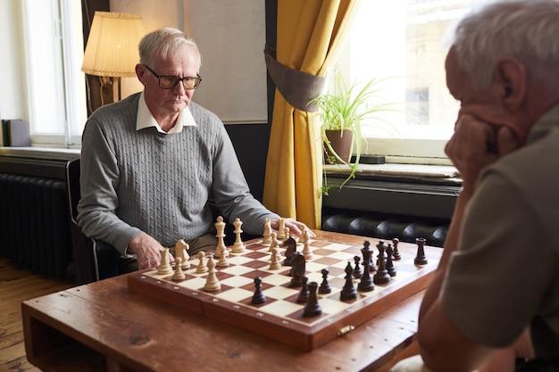 Retrato de homem caucasiano sênior jogando xadrez e desfrutando de atividades no espaço da cópia do lar de idosos