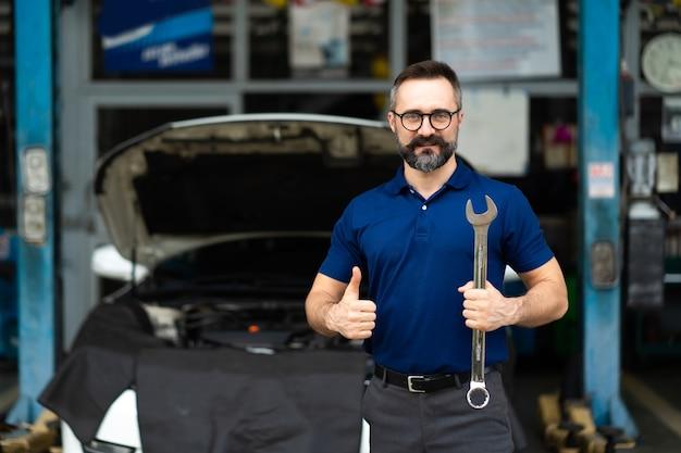 Retrato de homem caucasiano, sorrindo para a câmera e ferramentas de chave grande na mão. especialista em mecânico atuando em oficina mecânica.