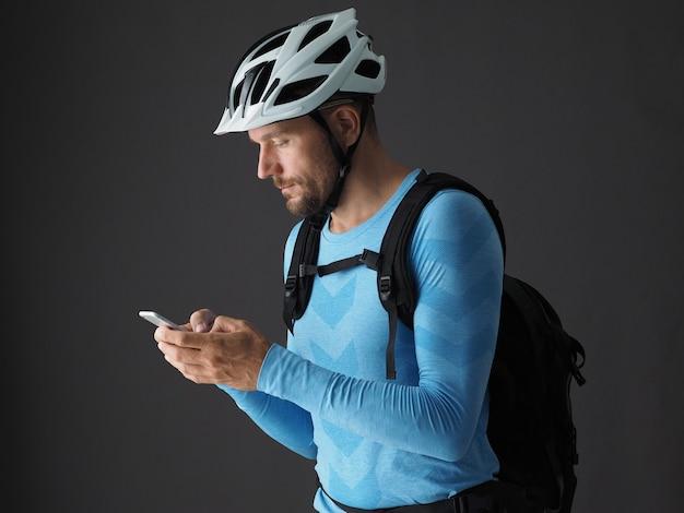 Retrato de homem ciclista com mochila usa smartphone antes da viagem. plano de fundo cinza.