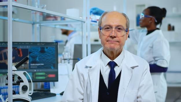 Retrato de homem cientista experiente sênior, sorrindo para a câmera no moderno laboratório equipado. equipe multiétnica examinando a evolução do vírus usando ferramentas de alta tecnologia e química para pesquisa científica, vacina d