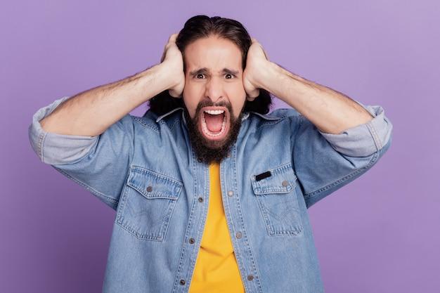 Retrato de homem cobrindo as orelhas em fundo roxo gritar gritar humor irritado