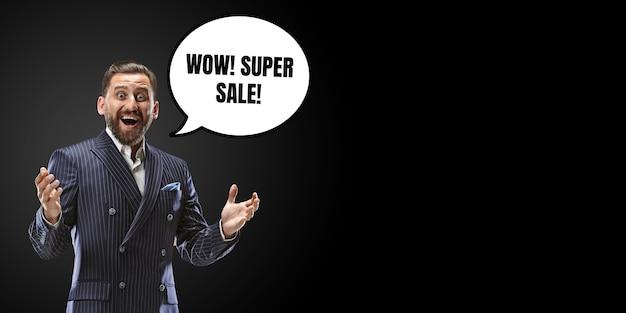 Retrato de homem com balão em fundo preto do estúdio. copyspace para sua publicidade. sexta-feira negra, cyber segunda-feira, vendas, dinheiro e dinheiro, conceito de compras e pagamentos online. chamada louca.