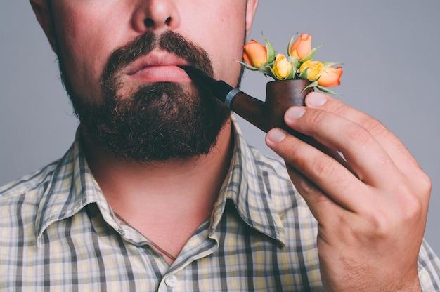 Retrato de homem com barba e cachimbo de fumaça com flores