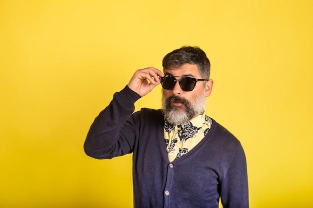 Retrato de homem com barba e óculos de sol, olhando para a câmera em fundo amarelo