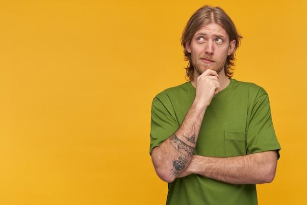 Retrato de homem com barba e penteado loiro a sonhar. vestindo uma camiseta verde. tem tatuagem. tocando seu queixo. observando atentamente à esquerda no espaço da cópia, isolado sobre a parede amarela