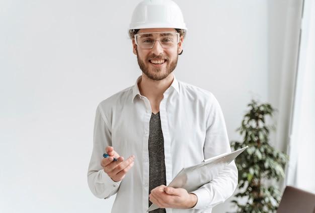 Retrato de homem com capacete no escritório