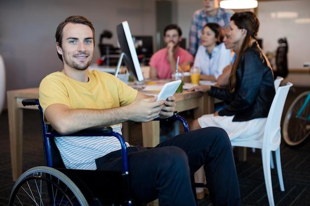 Retrato de homem com deficiência física em cadeira de rodas usando tablet no escritório