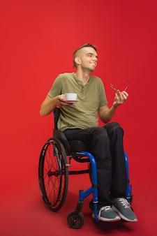 Retrato de homem com deficiência jovem caucasiano isolado no fundo vermelho do estúdio. conceito de emoções humanas