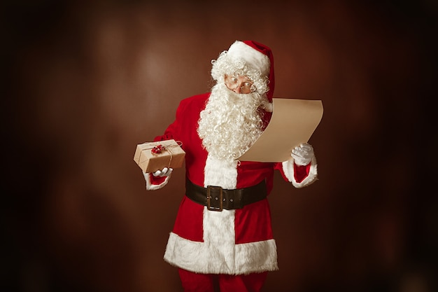 Retrato de homem com fantasia de papai noel - com uma luxuosa barba branca, chapéu de papai noel e uma fantasia vermelha lendo a carta no fundo vermelho do estúdio com presentes