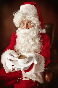 Retrato de homem com fantasia de papai noel - com uma luxuosa barba branca, chapéu de papai noel e uma fantasia vermelha no fundo vermelho do estúdio sentado em uma cadeira com uma xícara de café