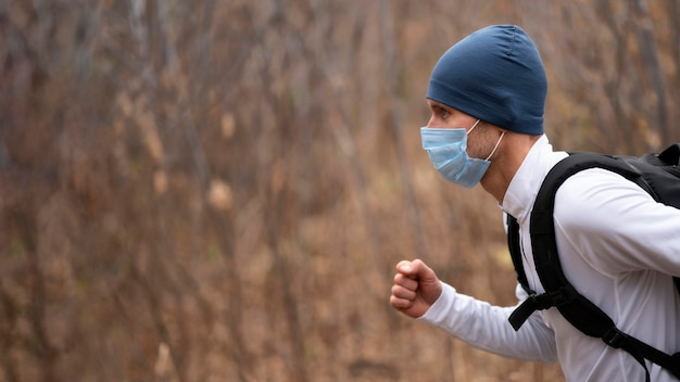 Retrato de homem com máscara facial correndo na floresta