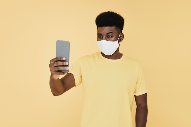 Retrato de homem com máscara facial olhando para smartphone