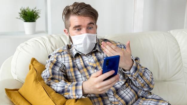 Retrato de homem com máscara facial segurando um celular