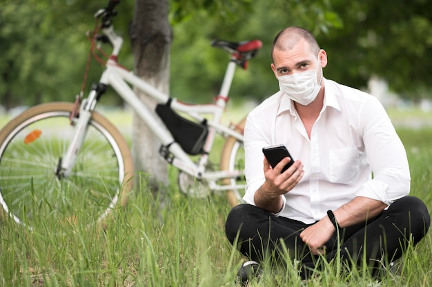 Retrato de homem com máscara médica ao ar livre
