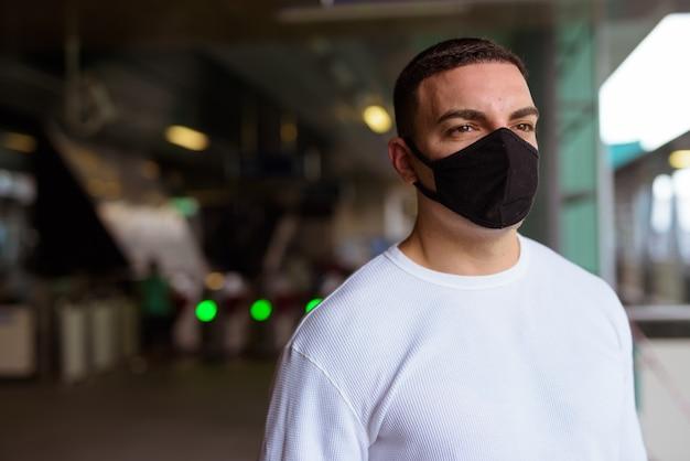Retrato de homem com máscara para proteção contra distanciamento social de surto de vírus corona na estação de trem do céu