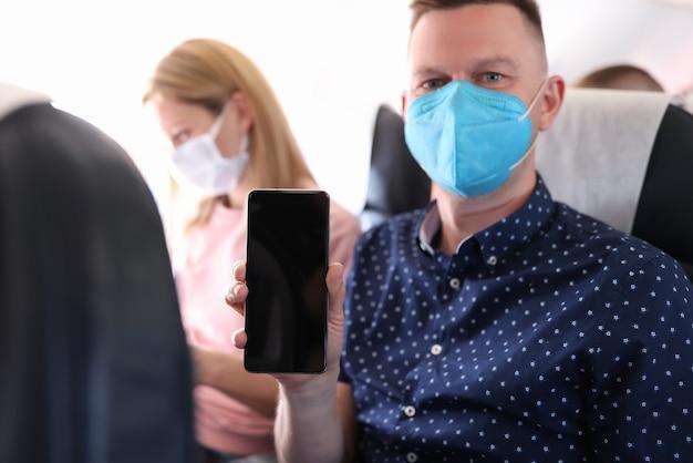 Retrato de homem com máscara protetora médica na cabine da aeronave em frente ao subwoofer segurando smartphone