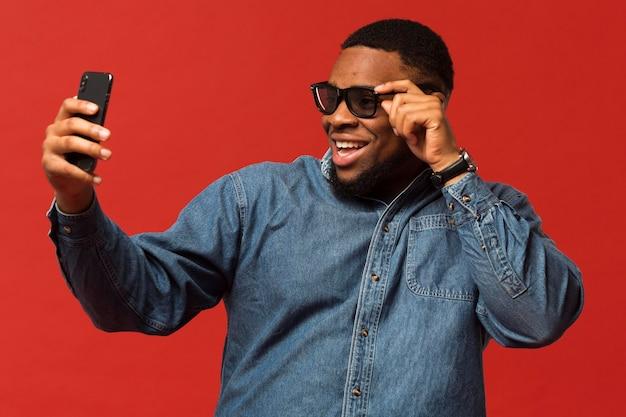 Retrato de homem com óculos escuros fazendo selfie