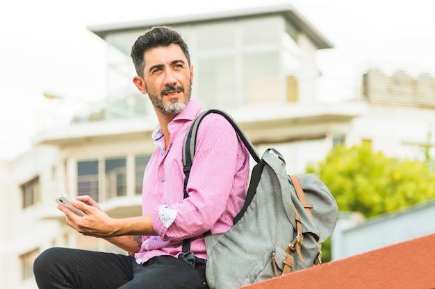 Retrato, de, homem, com, seu, mochila, usando, telefone móvel