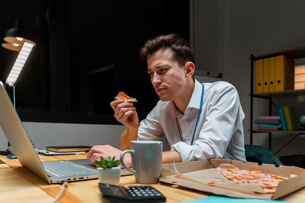 Retrato de homem comer um lanche enquanto trabalha em casa