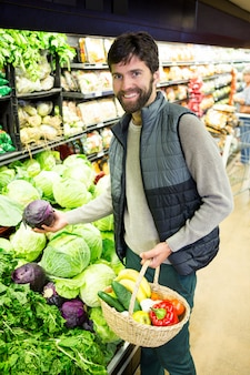 Retrato de homem comprando legumes na loja orgânica
