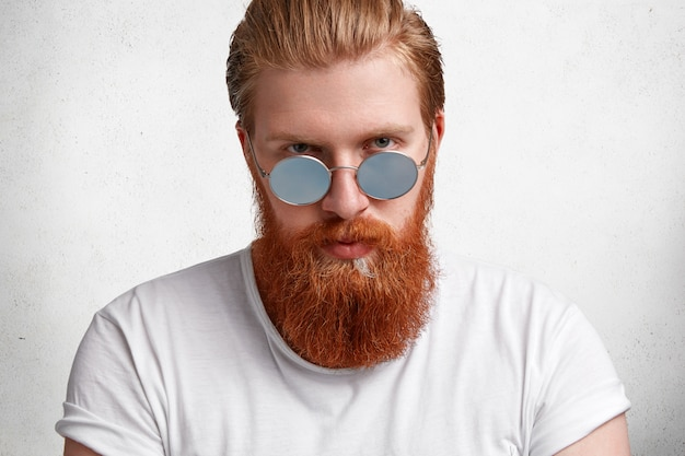 Retrato de homem confiante e brutal com corte de cabelo elegante, tem bigode e barba ruiva espessa e difusa, usa tons redondos e camiseta casual branca, posa sozinho contra a parede de concreto.