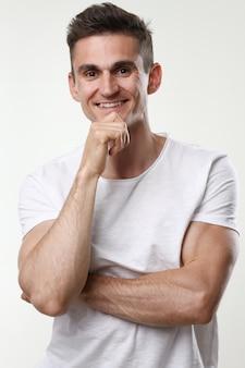 Retrato de homem de aptidão bonito em uma blusa branca sobre um fundo cinza