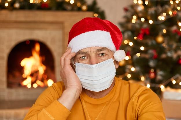 Retrato de homem de chapéu vermelho e máscara facial médica no rosto. celebração de natal durante a pandemia do vírus corona. homem infeliz de camisa amarela mantém a mão na cabeça, sente dor.