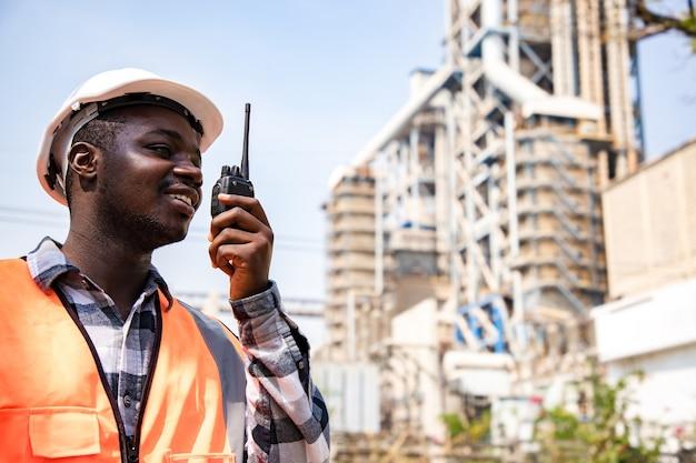 Retrato de homem de engenharia bonito usando walkie talkie e segurando a papelada com capacete de segurança de desgaste na frente da fábrica da indústria de petróleo. vista traseira do contratante no fundo de edifícios modernos.