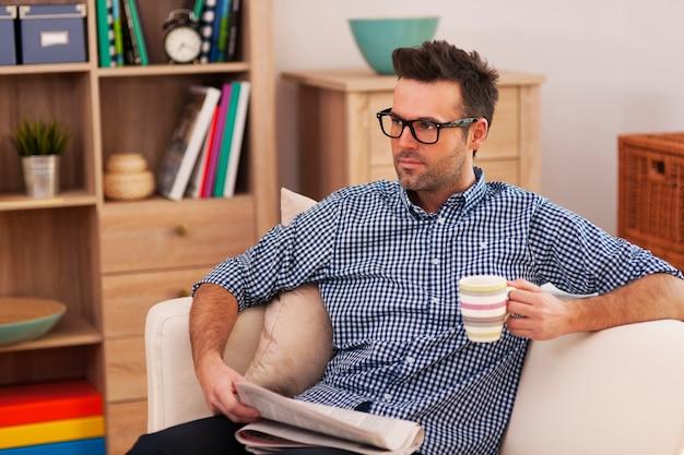 Retrato de homem de foco com jornal e xícara de café