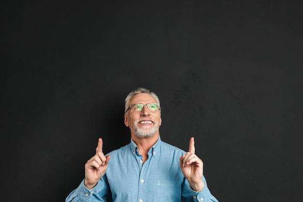 Retrato de homem de meia idade 50 anos com cabelos grisalhos e barba na camisa, sorrindo e apontando os dedos para cima na copyspace, isolado sobre a parede preta