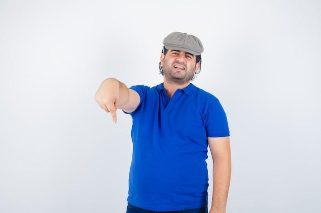 Retrato de homem de meia-idade apontando para baixo em camiseta polo e chapéu