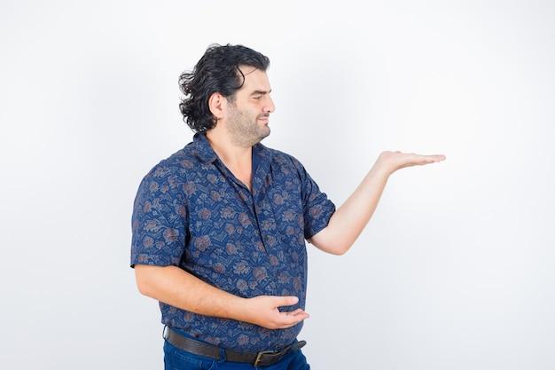 Retrato de homem de meia idade mostrando algo em uma camisa e olhando de frente feliz