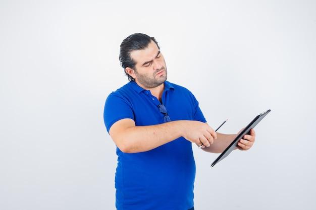 Retrato de homem de meia-idade olhando através da prancheta, segurando um lápis na camiseta polo e olhando de frente com atenção