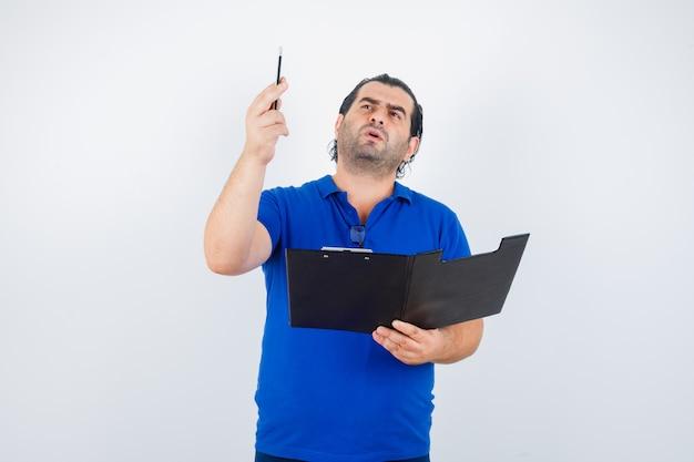 Retrato de homem de meia-idade olhando para cima enquanto segura um lápis e uma prancheta em uma camiseta polo e olhando pensativamente para a frente
